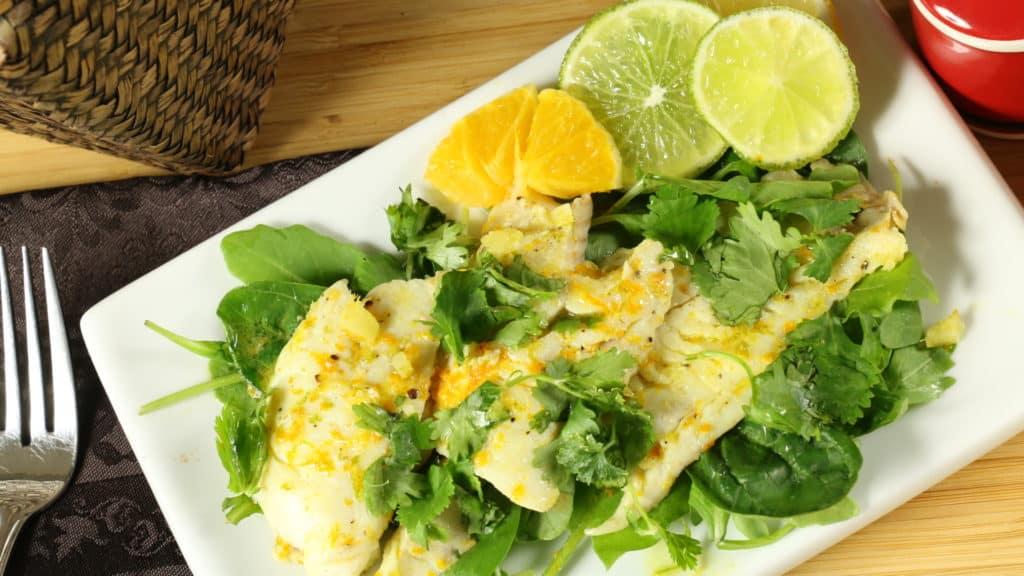 Assiette de poisson blanc aux agrumes avec citron et segments d'orange.