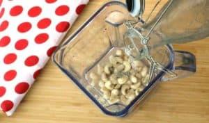 Mélangeur contenant de l'eau et des noix de cajou.